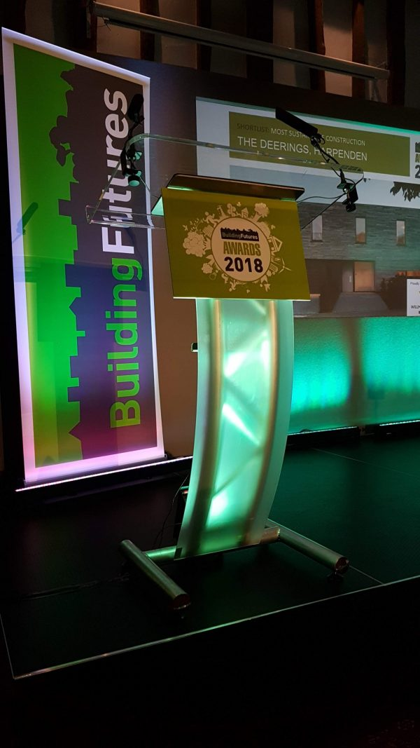 Curved perspex lectern with a foamex board with advertising attached to front.